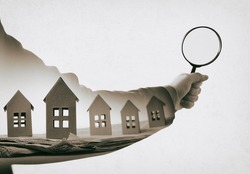 Hand with magnifier and paper houses on newspaper. Multiple exposure. Concept of real estate. Black and white.