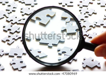 Hand with magnifying glass and puzzle isolated on white background