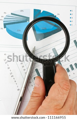 Hand with magnifying glass on a background of diagrams - stock photo