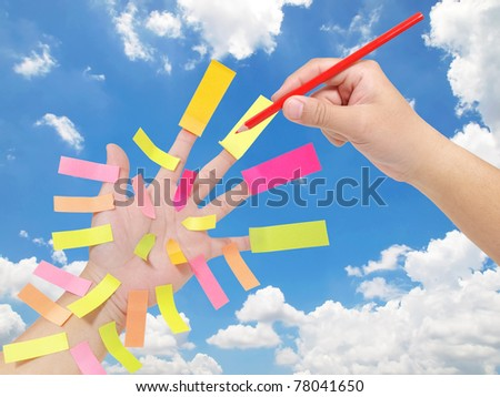 Hand with many blank sticky notes against blue sky