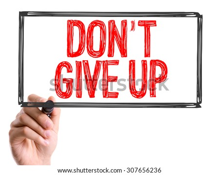 Hand with marker writing the word Don't Give Up