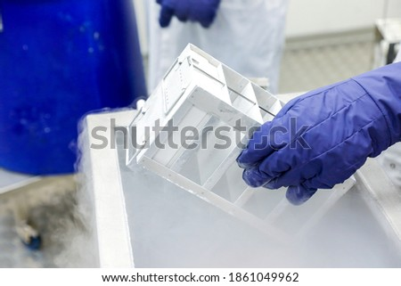 Hand with medical glove holding a bottle vaccine from ice storage. Medication treatment at nitrogen freeze. Stockfoto ©