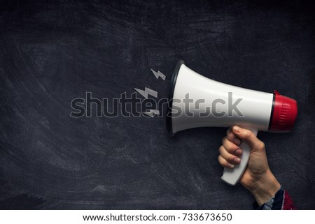 hand with megaphone on chalkboard with copy space