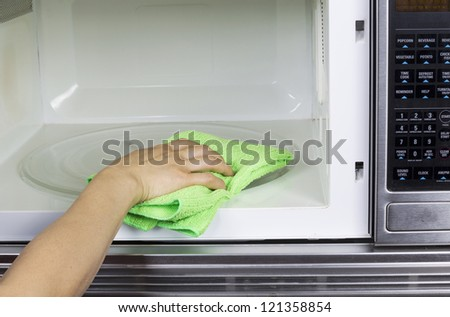 Hand with microfiber cleaning rag wiping inside of microwave oven #121358854