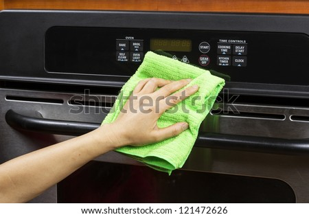 Hand with microfiber cleaning rag wiping outside of electric oven