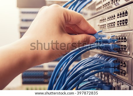 hand with network cables connected to servers in a datacenter