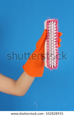 Hand with orange glove and cleaner brush in studio