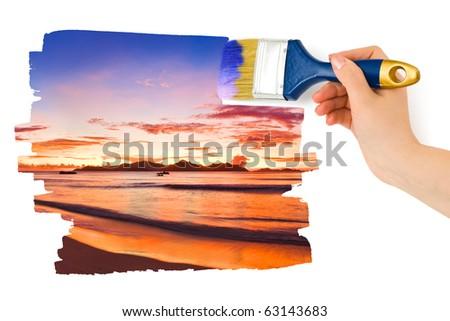Hand with paintbrush painting sunset isolated on white background