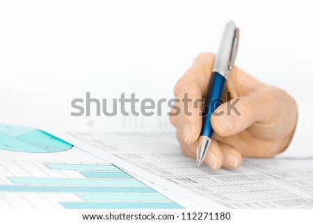 Hand with Pen Analyses Figures by Financial Charts and Graphs