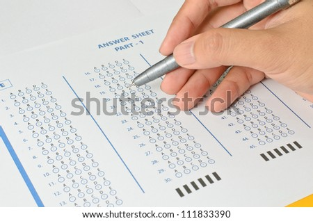 Hand with pen and Answer Sheet - stock photo