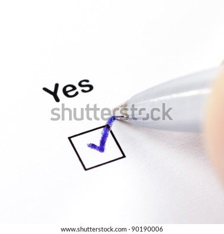 Hand with pen marks the check box Yes - stock photo