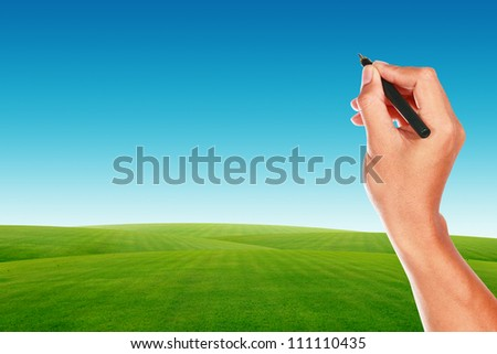 Hand with pen on blue sky and green grass