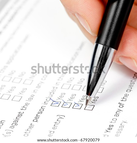 Hand with pen over blank check box Yes in application form
