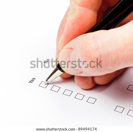 Hand with pen over blank check boxes in a form
