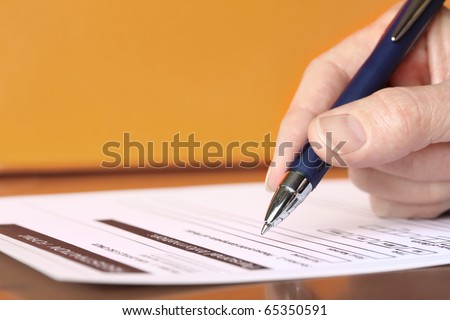 Hand with Pen Signing Form Closeup on Orange Background