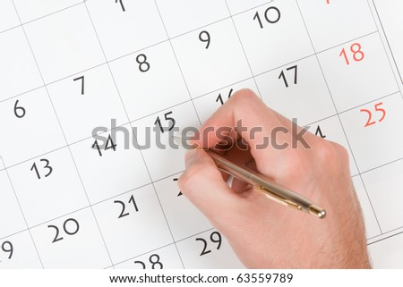 Hand with pen take a note into calendar