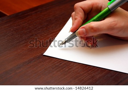 Hand with pen writing a letter