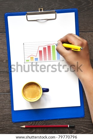 Hand with pen writing  on the clipboard and graph on it - stock photo