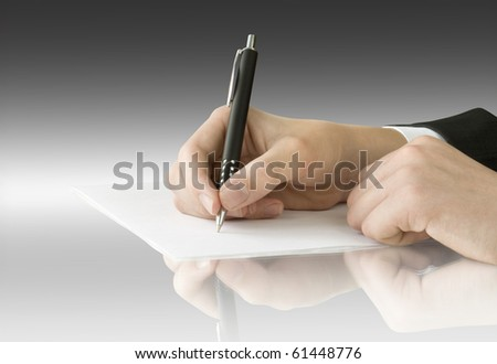 hand with pen writing on the page and reflection