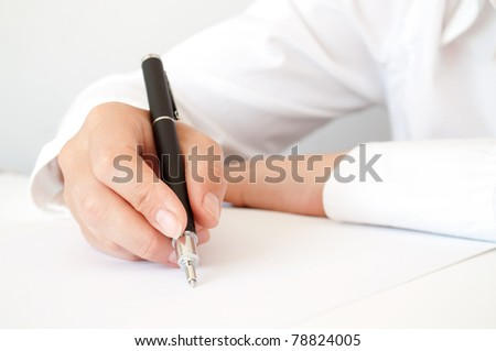 hand with pen writing on the white paper