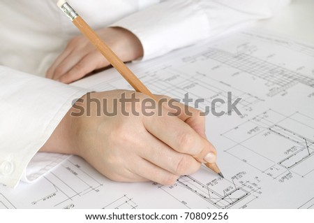 hand with pencil drawing construction plan