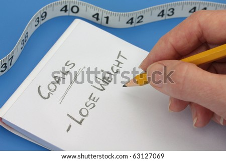 Hand with Pencil making goals list to lose weight - stock photo