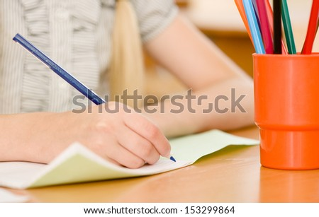 hand with pencil writing in a notebook