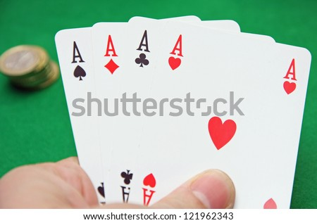 hand with poker of aces on a table game