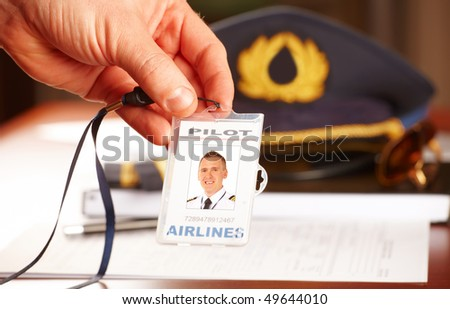Hand with professional airline pilot id holder, hat sun glasses laying on log book and flight plan in background