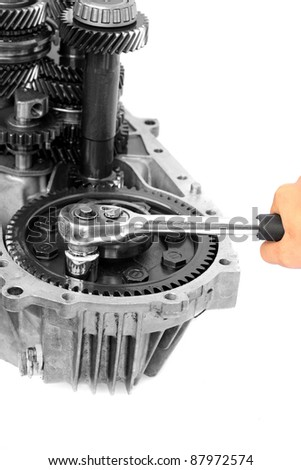 Hand with ratchet handle and mechanical gear on isolated white background