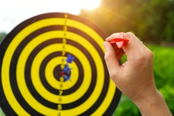 Hand with red arrow darts to throw on dartboard with isolated white and sunlight background, sport outdoor with arrows hitting the center target  also known as
