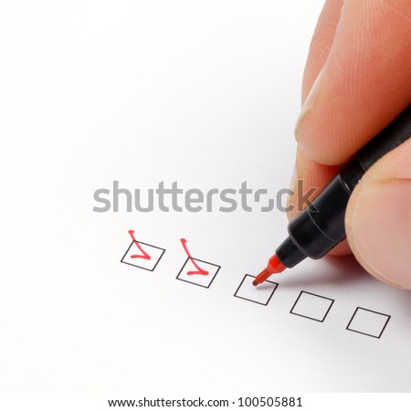 Hand with red pen marking a check box