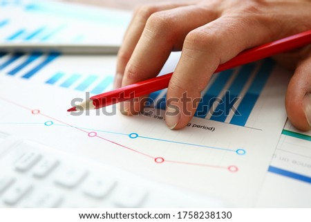Hand with red pencil lies on comparative chart. Build individual charts or view lead summary data. Dig deep into numbers and work with them manually. Comparative characteristics several companies Stock foto ©