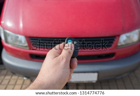 Hand with remote control directed red van. Pressing open button #1314774776