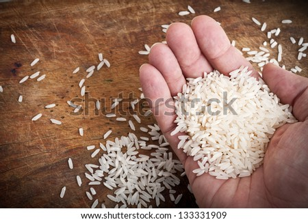 Hand with rice and wooden table.
