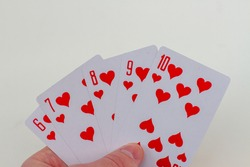 Hand with Royal Flush cards isolated on white background.