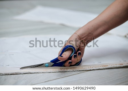 Hand with scissors with blue handles, cutting paper pattern with light beige fabric. Close-up picture of cutting process. Sewing tutorial. Pattern making workshop by fashion designer.