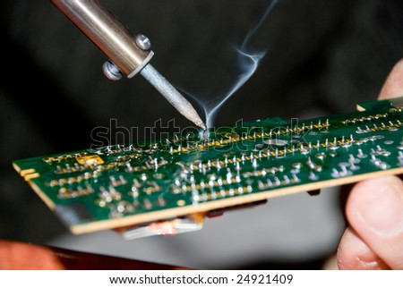 Hand with soldering iron