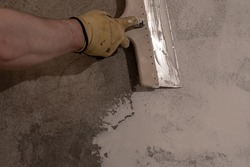 Hand with spatula applying layer of putty trowel, working with spackling paste.