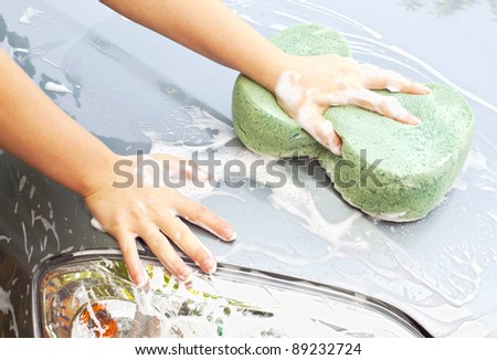 Hand with sponge cleaning car