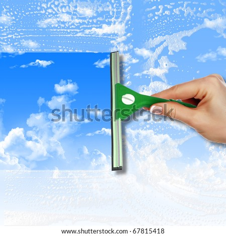 Hand with squeegee cleaning the  misted window - stock photo