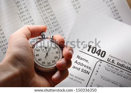 Hand with stopwatch on tax form and budget