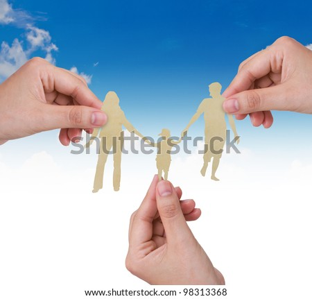 Hand with the paper cut of the family over blue sky