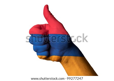 Hand with thumb up gesture in colored armenia national flag as symbol of excellence, achievement, good, - useful for tourism and touristic advertising