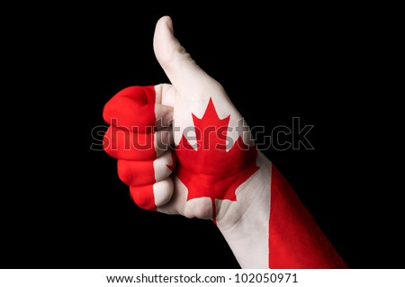 Hand with thumb up gesture in colored canada national flag as symbol of excellence, achievement, good, - for tourism and touristic advertising, positive political, social management of country