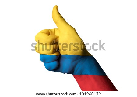 Hand with thumb up gesture in colored colombia national flag as symbol of excellence, achievement, good, - for tourism and touristic advertising, positive political, social management of country