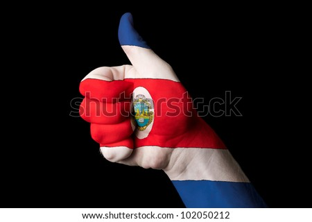 Hand with thumb up gesture in colored costa rica national flag as symbol of excellence, achievement, good, - for tourism and touristic advertising, positive political, social management of country