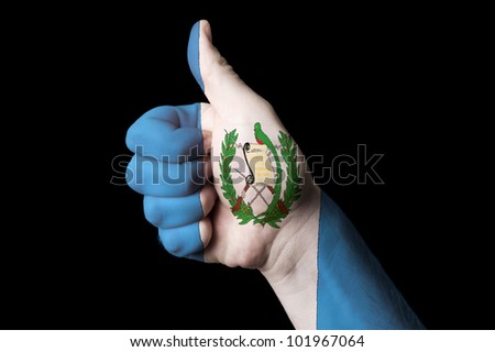 Hand with thumb up gesture in colored guatemala national flag as symbol of excellence, achievement, good, - for tourism and touristic advertising, positive political, social management of country