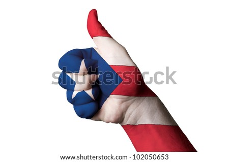 Hand with thumb up gesture in colored puertorico national flag as symbol of excellence, achievement, good, - for tourism and touristic advertising, positive political, social management of country