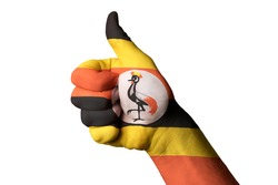 Hand with thumb up gesture in colored uganda national flag as symbol of excellence, achievement, good, - for tourism and touristic advertising, positive political,  social management of country